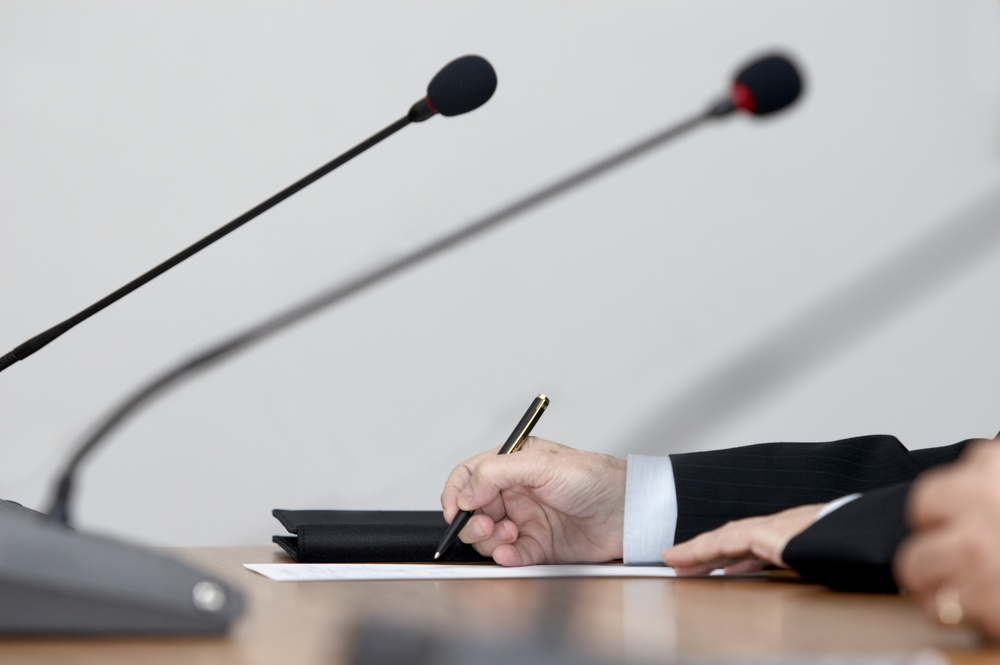 close up of conference meeting microphones and businessman writing